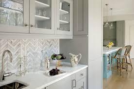 marble tiled chevron backsplash with light grey cabinetry