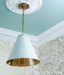 a minimalist pendent by circa lighting with handsome brass detailing punctuates the robin s egg blue painted