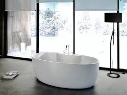 grey bathroom walls sumptuous white glossy ceramic bathtub herringbone tile floor dark stone wall and exposed
