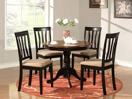 round kitchen table complete with 4 chairs and flower vase plus white ceramics teapot and cups in the dining room with wooden floor plus round carpet also
