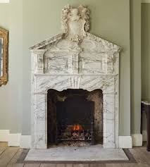 this magically ornate marble fireplace with a stunningly intricate mantel looks like it could have been built inside of a far away fairy tale like castle