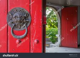 closed up of vine chinese lion door knocker on red wooden door the lion hold