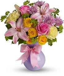 graceful and gorgeous describes this stunning array of pastel flowers in a charming lavender vase tied with a pink satin ribbon it s almost too pretty for