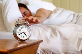 a man reaching out for an alarm clock while still in bed