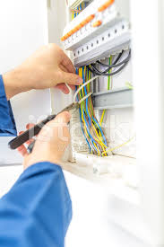 electrician checking the wiring in a fuse box stock photos electrician checking the wiring in a fuse box