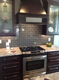 gray glass subway tile backsplash with dark brown cabinets and stainless steel appliances