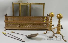 small pierced brass fireplace fender a pair of brass andirons a small brass folding four panel fireplace screen and a pair of firepl