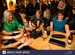 office party christmas pub stock photos office party christmas a group of women friends laughing and enjoying themselves playing a drinking game in a pub