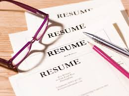 pile of resumes with glasses and pen post your resume on indeed