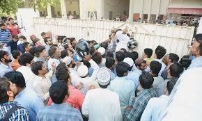 driving licence drive postponed amid chaos at traffic police  a number of applicants try to squeeze through the gate of the nazimabad driving licence branch