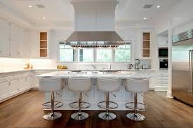 fabulous gourmet kitchen features a ceiling mount vent hood suspended over an island cooktop lined with white leather barrel back counter stools with silver