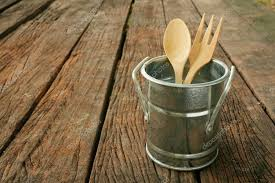 the small vintage zinc pot with wooden spoon and fork on the old dark brown wooden