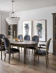 side by side black and gold abstract art piece hang on a white wall between tall gl cabinets and behind an oval french dining table surrounded by black