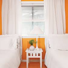 Bedroom With Orange Walls And White Twin Beds