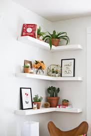 white solid wood corner living room floating shelves brownish plastic plant pots small white ceramic flower
