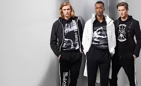 three men in monochrome shirts with vintage athletic poster graphics
