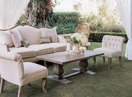 rustic elegant furniture. plush sofa chair and wood coffee table on grass at wedding reception rustic elegant furniture i