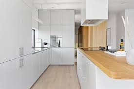 the kitchen features a sleek modern mix of white millwork and natural wood countertops