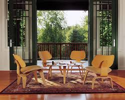 by molding lightweight plywood veneer into gently curved shapes the eameses created their classic molded plywood lounge chair with wood base