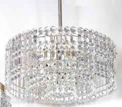 dramatic drum chandelier composed of three layers of rectangular faceted crystal prisms on a polished nickel