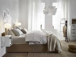 A medium sized bedroom furnished with a a white-stained oak MALM bed,  hanging EKET