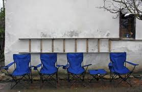 Each is designed with a curved back for. Empty Blue Folding Camping Chairs And Table Lined Up In Front Of A Rustic White Wall With A Ladder On The Wall Stock Images Page Everypixel