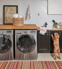 a red and brown vintage rug sits in front of an lg washer and dryer enclosed beneath a blond wood countertop topped with a framed art piece
