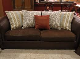 brown sofa featuring striped plus tendrils and deep orange decorative pillows