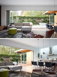 contemporary house furniture. This Modern Open-plan Living Room Looks Out Onto The Patio Through A Wide, Glass Folding Wall System. Gray, Green, Brown, And Wood Furniture Match Contemporary House