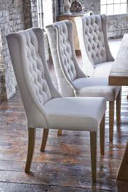 upholstered winged chairs will give your dining room an air of elegance we love the kipling chair with its chic curved legs to