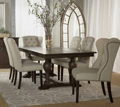 exclusive white tufted cowhide dining chair with white orchid on the wooden table with arch entrance