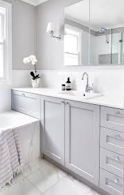 Beautiful gray and white bathroom is fitted with a a gray washstand  adorning polished nickel knobs and a white quartz countertop holding an  overmount sink ...