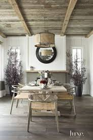reclaimed wood from the vine wood floor pany lines the ceiling and gives a rustic feel to the dining room a drum shade pendant by lowcountry