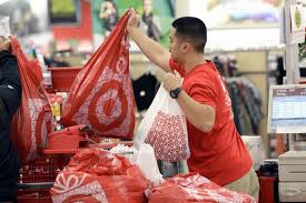 a target employee hands bags to a customer at the register