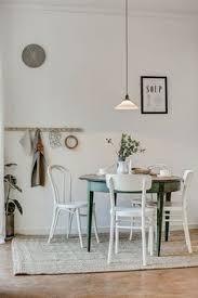 un coin repas au style chêtre avec sa table en bois verte et ses chaises de scandinavian dining roomsdining