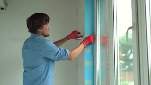 A Young Man Installing Plastic Window Installer Fills The Slope Of Plastic Window With A Mounting Foam