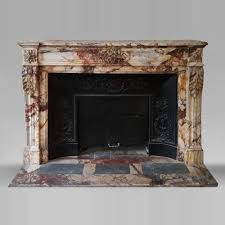 an antique louis xvi style fireplace made out of black marble decorated with a