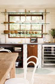 stand kitchen dsc: home tour a stylish hawaiian island escape via domainehomea beautiful set of floating shelves on brass brackets creates balance between the kitchens