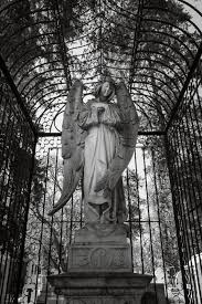 candlelit day of the dead ofrendas in jalisco ⋆ photos of  a statue of a stone angel inside a cage in the panteon municipal in morelia