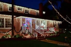 outside christmas lighting. santa in the window of home with colorful outdoor christmas lighting outside