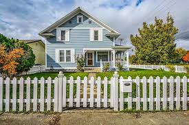 picket fence design. White Picket Fence Design Surrounding A Charming Home With Large Front Porch