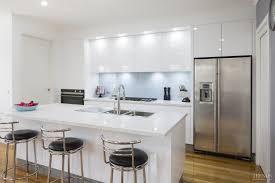 Sleek, contemporary white kitchen with pale blue glass splashback ...