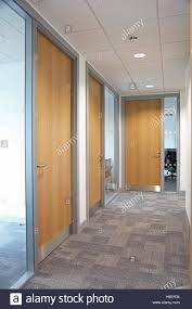 modern office door. Corridor In A Modern Office Building Showing Glazed Partition Walls, Grey Carpet And Timber Fire Doors Door