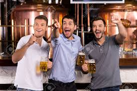 goal three happy men holding beer mugs and gesturing while three happy men holding beer mugs and gesturing while watching tv in bar stock