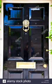 a shiny high gloss black painted front door with highly polished brass door furniture