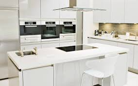 white kitchen design with built in electric cooktop and sink kitchen island under glass canopy range hood