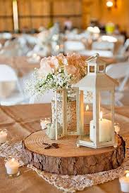 a wood slice with a white candle lantern and a rustic fl arrangement in a jar