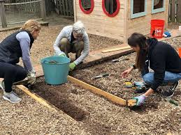 members of the junior league of greenwich help to install a new learning garden at the