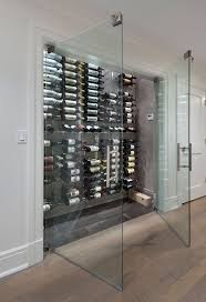 Glass doors for wine closet Seamless glass double doors open to a wine  closet fitted with floor to ceiling wine racks.