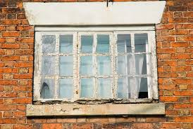 window in need of repair on a red brick house